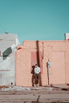 Un homme hipster élégant posant les bras croisés sur le trottoir dans la banlieue