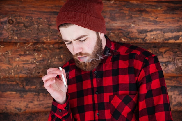 Homme de hipster fumant sur la maison en bois
