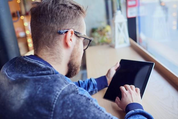 Un homme hipster indépendant avec tablette dans sa main travaille café par t
