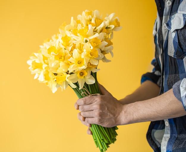 Homme de hipster sur un mur jaune dans une chemise et un bouquet de fleurs.
