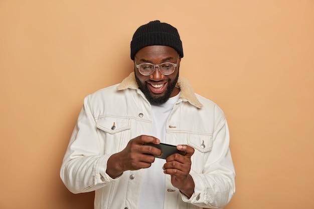 Homme hipster noir avec expression positive joue à des jeux vidéo