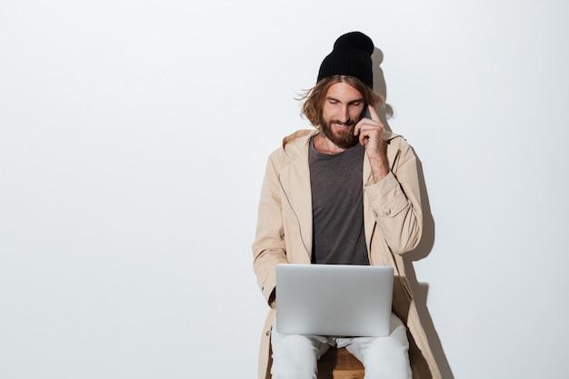 Homme de hipster regardant de côté avec un ordinateur portable