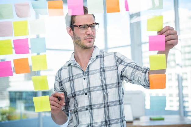 Homme hipster regardant post-it au bureau