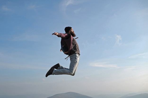 Homme hipster saute avec sac à dos bonheur insouciant liberté concept hipster homme avec barbe et moustache en chapeau saute avec hache sur le sommet de la montagne sur ciel nuageux