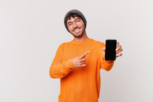 Homme hispanique avec une cellule semblant excité et surpris pointant vers le côté et vers le haut pour copier l'espace