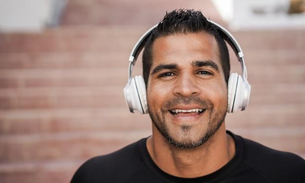 Homme hispanique, écouter de la musique avec des écouteurs - focus sur le visage