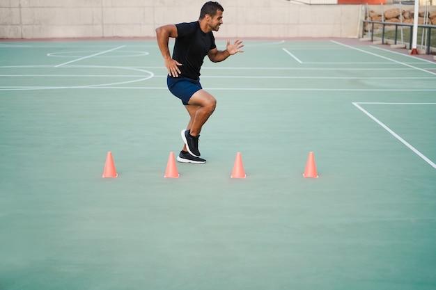 Un homme hispanique faisant des exercices de cône de vitesse et d'agilité à l'extérieur - focus sur le visage de l'homme