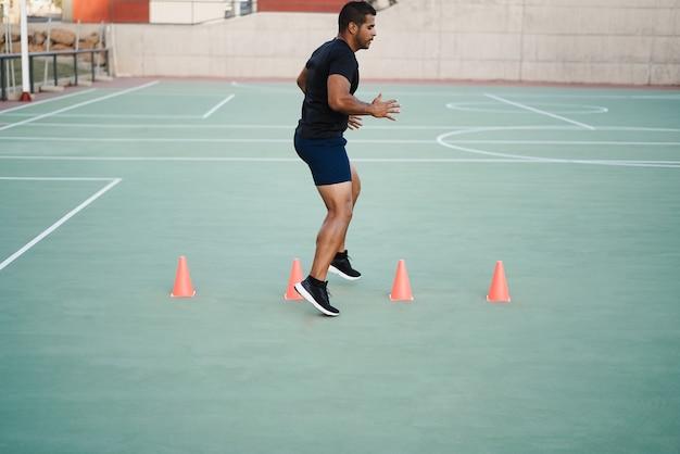 Homme hispanique faisant des exercices de cône de vitesse et d'agilité à l'extérieur