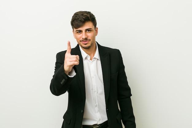 Homme hispanique de jeunes entrepreneurs montrant le numéro un avec le doigt.