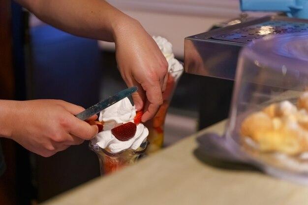 Homme hispanique mettant des fraises dans un verre avec de la crème glacée et de la crème