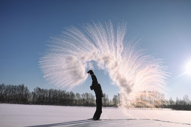 Un homme en hiver dans la rue. le gars marche sur la route d'hiver. un jeune homme en doudoune saute dans la neige.