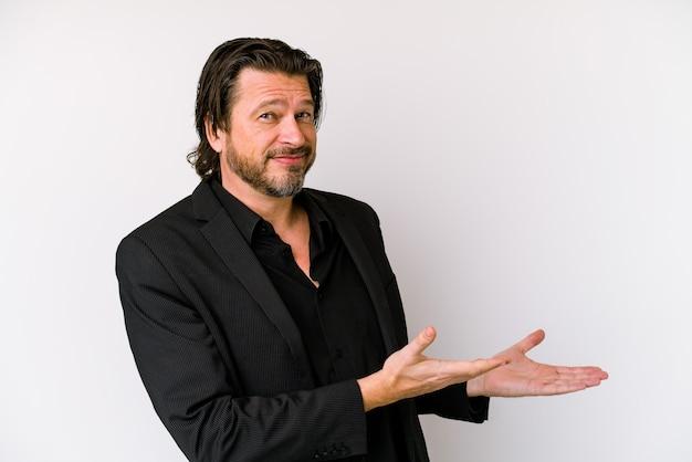 Homme hollandais d'affaires d'âge moyen isolé sur un mur blanc tenant un espace de copie sur une paume.