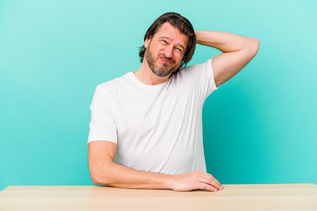 Homme hollandais d'âge moyen assis isolé sur un mur bleu touchant l'arrière de la tête, en pensant et en faisant un choix.