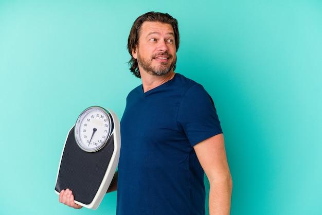 Homme hollandais d'âge moyen tenant une échelle isolée sur un mur bleu regarde de côté souriant, gai et agréable