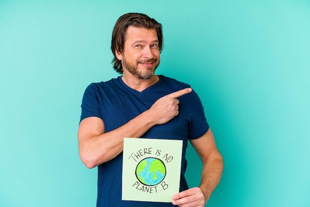 Homme hollandais d'âge moyen tenant un il n'y a pas de plaque-étiquette de planète b isolée sur un mur bleu souriant et pointant de côté, montrant quelque chose à l'espace vide