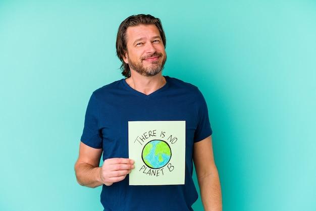 Homme hollandais d'âge moyen tenant un il n'y a pas de plaque de planète b isolée sur un mur bleu heureux, souriant et gai