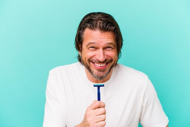 Homme hollandais d'âge moyen tenant une lame de rasoir isolée sur mur bleu en riant et en s'amusant