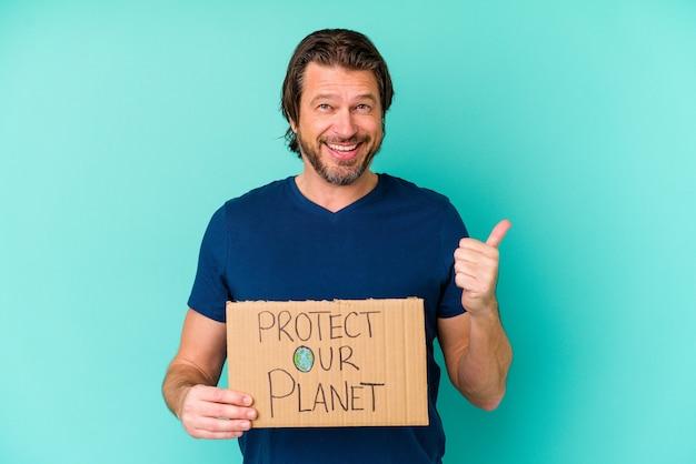 Homme hollandais d'âge moyen tenant une pancarte protéger notre planète isolée sur mur bleu en souriant et en levant le pouce vers le haut