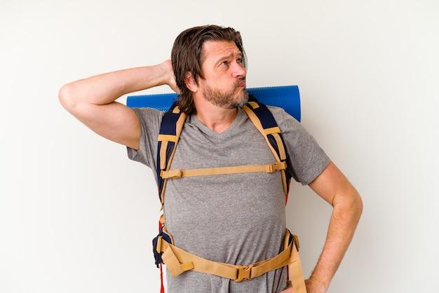 Homme hollandais randonneur d'âge moyen isolé sur un mur blanc touchant l'arrière de la tête, en pensant et en faisant un choix