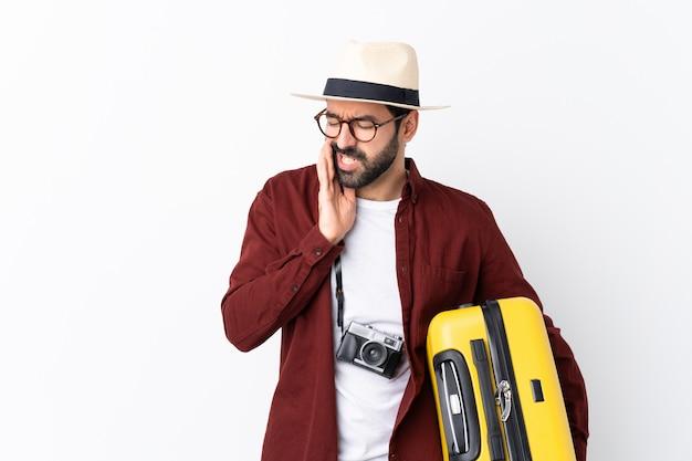 Homme homme voyageur avec barbe tenant une valise sur un mur blanc isolé avec des maux de dents