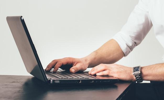 L'homme avec une horloge sur sa main travaille sur l'ordinateur portable à la table du bureau. il est occupé avec la tâche