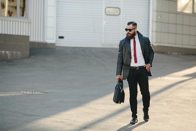L'homme en imperméable en cuir et porte-documents