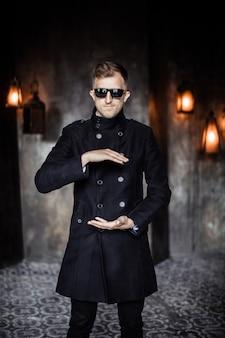 L'homme en imperméable et lunettes de soleil tient ses mains comme s'il y avait quelque chose entre eux