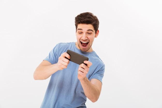 Homme impliqué dans un t-shirt décontracté, jouer à des jeux en ligne sur téléphone portable, isolé sur mur blanc