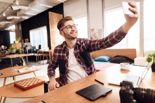 Homme indépendant prenant selfie devant un ordinateur portable assis au bureau.