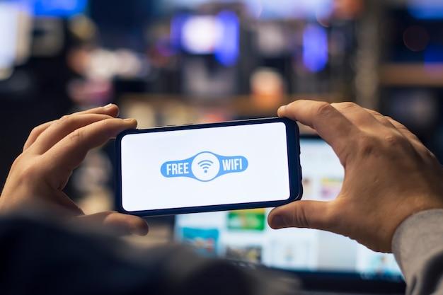 L'homme indépendant tient un smartphone avec internet gratuit dans ses mains sur le fond d'un ordinateur portable.