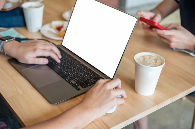 Homme indépendant travaillant avec un ordinateur portable d'affichage vide et une tasse de café sur une table en bois dans un café