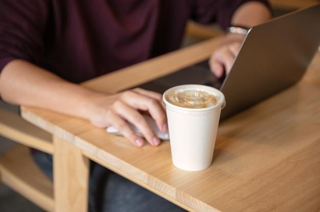 Homme indépendant travaillant avec un ordinateur portable et une tasse de café sur une table en bois dans un café