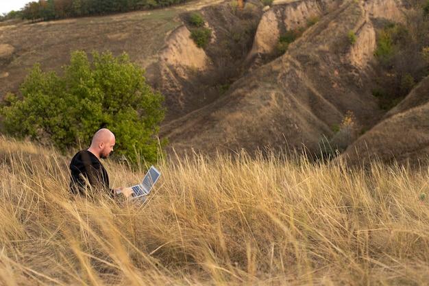 Homme indépendant travaillant parmi les montagnes dans la nature