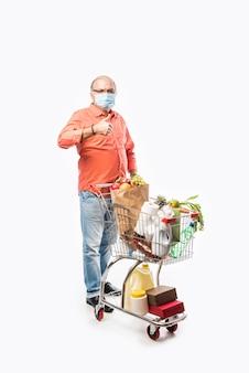 Un homme indien âgé ou âgé porte un masque facial transportant un panier ou un chariot rempli d'épicerie, de légumes et de fruits. photo pleine longueur isolée sur mur blanc