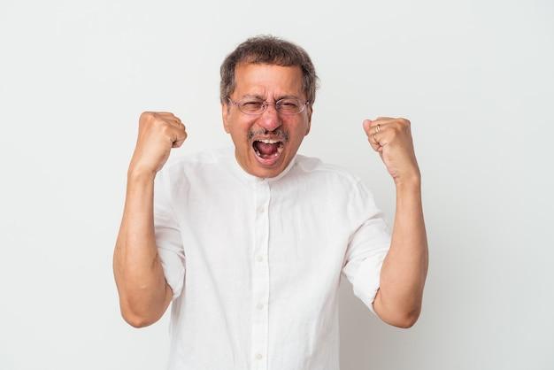 Homme indien d'âge moyen isolé sur fond blanc acclamant insouciant et excité. notion de victoire.