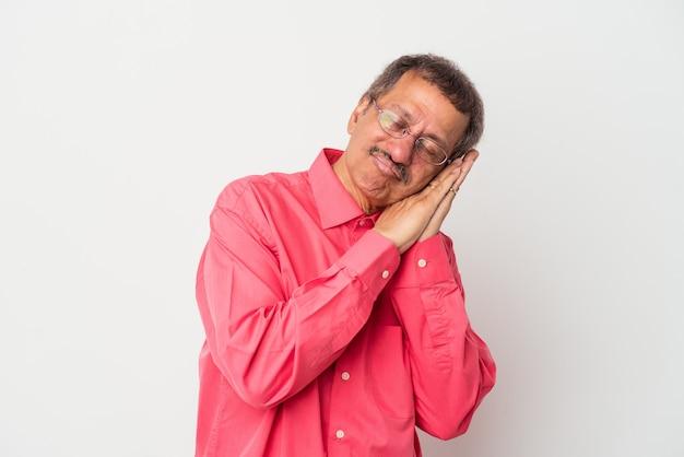 Homme indien d'âge moyen isolé sur fond blanc bâillant montrant un geste fatigué couvrant la bouche avec la main.