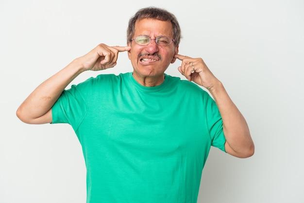 Homme indien d'âge moyen isolé sur fond blanc couvrant les oreilles avec les doigts, stressé et désespéré par une ambiance bruyante.
