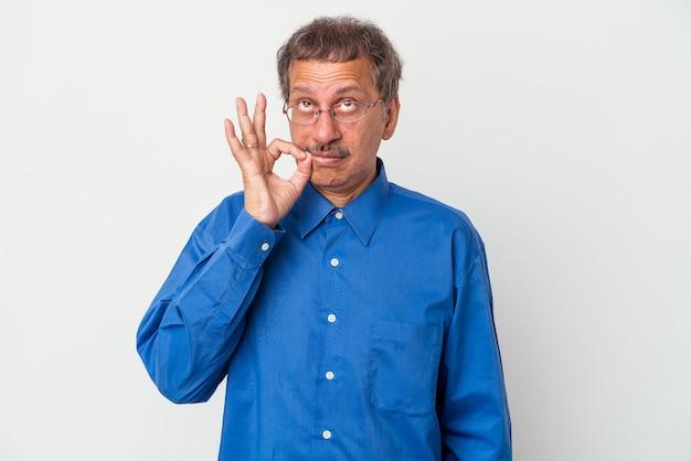 Homme indien d'âge moyen isolé sur fond blanc avec les doigts sur les lèvres gardant un secret.