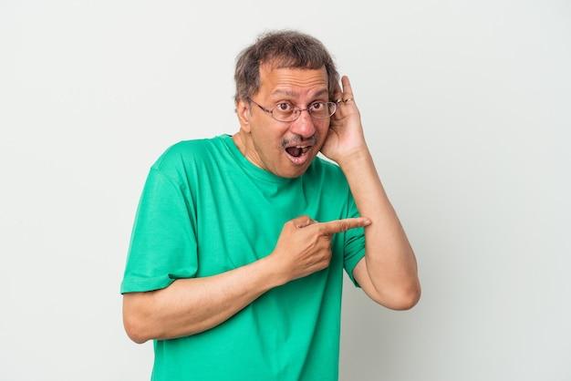 Homme indien d'âge moyen isolé sur fond blanc essayant d'écouter un potin.