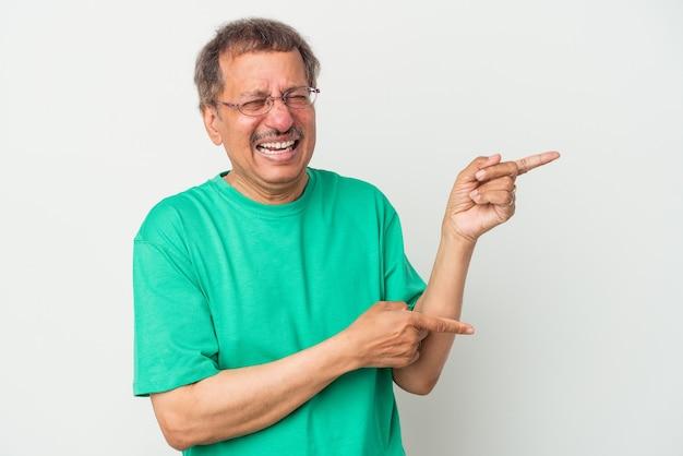 Homme indien d'âge moyen isolé sur fond blanc excité pointant avec les index loin.