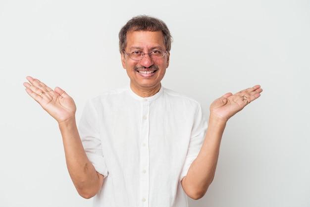 Un homme indien d'âge moyen isolé sur fond blanc fait de l'échelle avec les bras, se sent heureux et confiant.