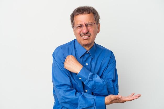 Homme indien d'âge moyen isolé sur fond blanc massant le coude, souffrant après un mauvais mouvement.