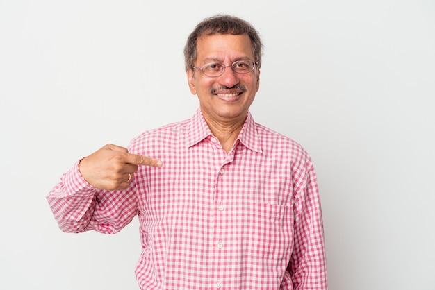 Homme indien d'âge moyen isolé sur fond blanc personne pointant à la main vers un espace de copie de chemise, fier et confiant