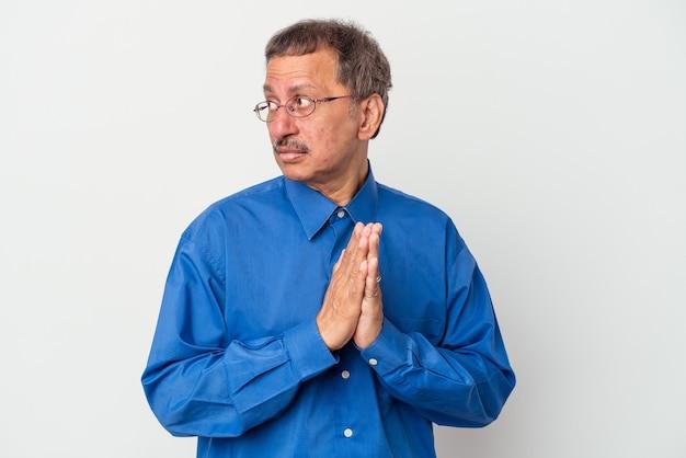 Homme indien d'âge moyen isolé sur fond blanc priant, montrant la dévotion, personne religieuse à la recherche d'inspiration divine.