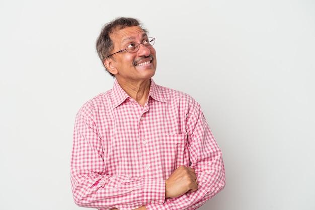 Homme indien d'âge moyen isolé sur fond blanc rêvant d'atteindre des objectifs et des buts
