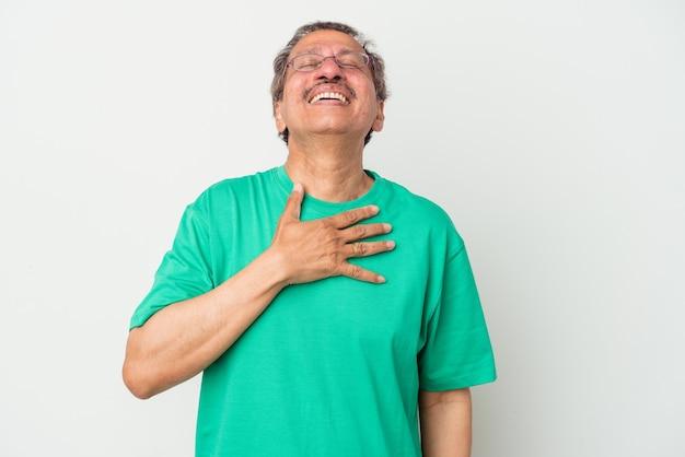 Homme indien d'âge moyen isolé sur fond blanc rit fort en gardant la main sur la poitrine.