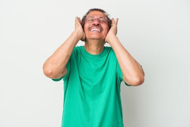 Homme indien d'âge moyen isolé sur fond blanc rit joyeusement en gardant les mains sur la tête. notion de bonheur.