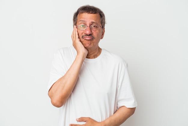 L'homme indien d'âge moyen isolé sur fond blanc souffle les joues, a une expression fatiguée. concept d'expression faciale.