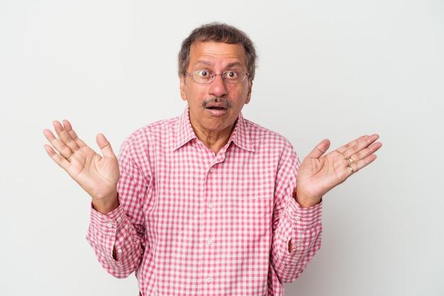 Homme indien d'âge moyen isolé sur fond blanc surpris et choqué.