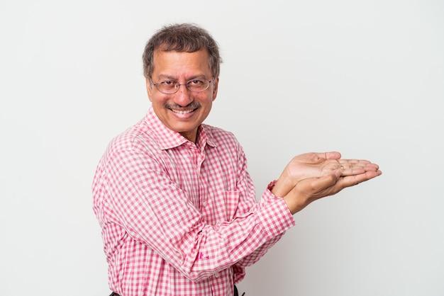 Homme indien d'âge moyen isolé sur fond blanc tenant un espace de copie sur une paume.